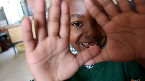An image of a child looking through his hands.